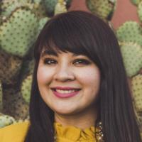 Photograph of Reyna Montoya in a front of a prickly pear cactus