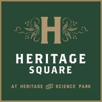 "Heritage Square Logo (A gold letter ""H"" centered on a dark green background with floral ornaments on either side)"