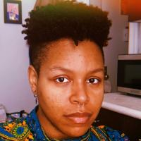 Cyrée Jarelle Johnson, a black transmasculine person with medium brown skin, a septum ring, and a nostril ring. He wears a shirt with a very loud print: gold circles surrounded by teal squares. Three buttons go up to the neck of the collarless shirt. His