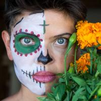 Photograph of Myriam Gurba's face half-painted like a skeleton for Dia De Los Muertos, partially obscured by flowers